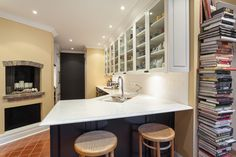 Traditional kitchen with lots of display glass cabinets, dark lower cabinets and a dining area for two.