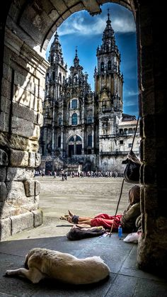 The end of the journey - Pelgrim and his companion resting under the arches of Santiago City Hall staring at The Cathedral - Galicië - Spain - by Juan Figueirido