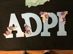Adpi wooden painted decorated letters. Blue paint, white flowers, diamond gems in white flowers, and Violet's all for adpi symbols!