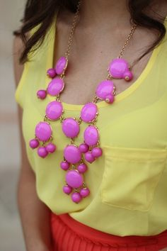 Contrasting colors. Pink statement necklace over a yellow tank with orange skirt.