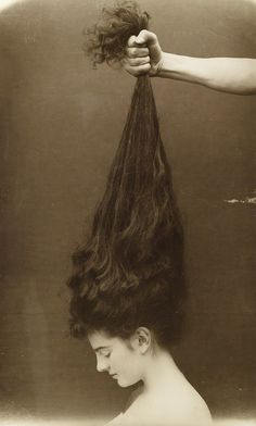 Hand grasping a young woman's long, dark hair. c1910