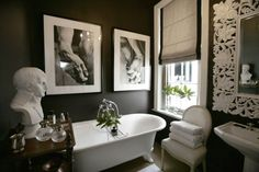 Chic black & white bathroom design with clawfoot  tub, black walls paint color, white pedestal sink, white ornate mirror, linen oval back Louis chair, black and white roman shades and black & white photo gallery.