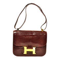 Vintage Hermes 22cm Constance in Burgundy Crocodile with Gold Hardware.   From a collection of rare vintage handbags and purses at https://www.1stdibs.com/fashion/accessories/handbags-purses/