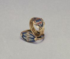 1400-12-- BC, egyptian. Gold with glass,lapiz lazuli and carnelian inlay. One ring of this pair has a slender hoop attached to a lentoid bezel on which opposing lotus blossoms with petals of alternating dark and light blue glass are cut and set into gold cloisons. The cloisons between the petals are filled with white glass with purple specks. Lotus blossoms were a popular motif and symbolized regeneration.