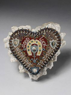 An English pincushion, handmade in c.1900 from silk, beads, pins and photographs; in the form of a heart, containing photographs of military figures from the Boer War; the slogan reads 'Good luck, with love to Jack' with a lucky horseshoe and blue anchor (a symbol of hope); Jack may have been a soldier and the pincushion may have been displayed at home. (Victoria & Albert Museum)
