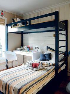 O dono deste quarto dorme sozinho, mas tem um lugarzinho extra para receber os amigos. Mesa e cadeira couberam no vão ao lado da cama inferior. Projeto da arquiteta Paula Radomille