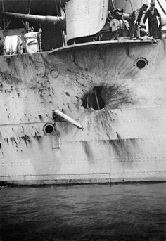 A shell-hole in the side of HMS Chester sustained at the Battle of Jutland 31 May 1916. Visible on deck is a 5.5-inch gun.