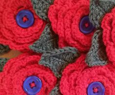 Red crochet buttonholes with blue button centres and green leaves. Commissioned for a wedding. © LIsa Benjamin www.handmadeflowers.co.uk