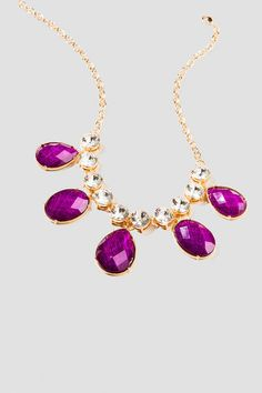 """Add a regal statement to your evening look with the Rohan Statement Necklace. Large, glittering purple jewels hang from a string of reflective crystals for a bold statement. With a simple dress, the Rohan Statement Necklace will be perfect for an evening out or sparkly addition to Game Day.<br />  <br />  - 18"""" length<br />  - 3"""" extension<br />  - Lobster claw clasp<br />  - Lead and nickel free<br />  - Imported"""