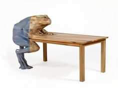 Frog Table (above) is a solid, walnut wood table with a frog appearing to climb onto one corner. The frog is partly coated in blue, transparent enamel.