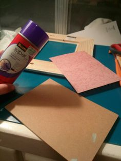 Use spray adhesive on cardboard then place paper on top. Give it a second to dry.