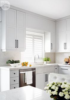 "Custom grey cabinets—The cabinet doors open up to reveal ceiling-high storage space. ""We went with a fairly streamlined profile to keep the look minimalistic,"" says designer Stacey Cohen. ""Painting the cabinets white would have been too stark, so we coated them in a soft grey to tie in with the transitional bones of the home."""