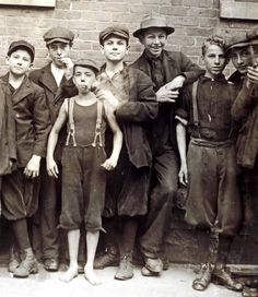 KID EMPLOYEES: Mill boys. Picture taken between 1913-1916. The smallest one has no over shirt or shoes, but seems to enjoy his pipe.