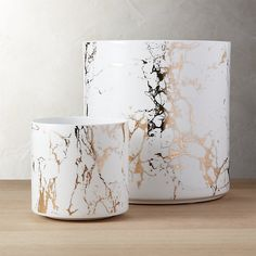 Shop palazzo marbleized planters.   Thin ceramic cylinders mimic marble with a metallic twist.  Gold metallic decal on bright white plants indoor greens in style.