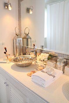Bathroom with metallic tile around the mirror, vessel sink, mercury glass accents