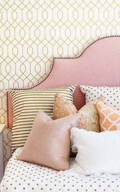 Dainty gold details: trellis wallpaper, nailhead trim, striped pillow shams, and sparkly dot bedding.