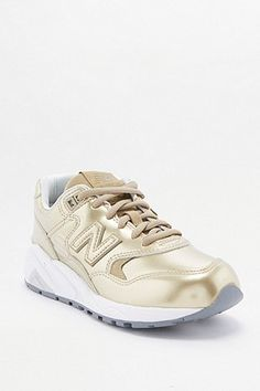 on sale 5d696 1caae New Balance 580 Metallic Gold Trainers Urban Outfitters