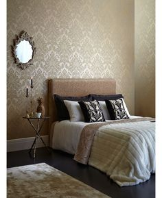 This beautiful Glisten Damask wallpaper features a raised damask pattern in a soft gold tone with added light reflecting glitter particles, on a vibrant gold background that is infused with a subtle mica sheen.