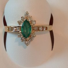 14 Kt Marquie Emerald Ring 14 Kt Yellow Gold, 7x3.5 Marquie Emerald with 10 Round Prong Set Diamonds and 6 Round Channel Set Diamonds Jewelry Rings