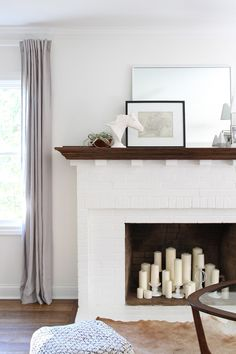 Fireplace filled with lots of pillar candles - Room for Tuesday