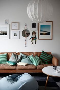 living room- white walls, brown sofa, simple but eclectic gallery wall, green pillows