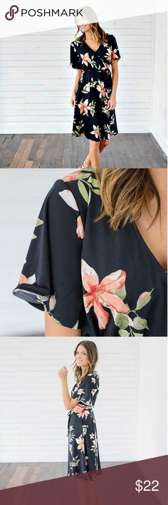 """Black Floral Wrap Gorgeous floral faux wrap. Only worn once. I'm 5'0"""" and it falls about 3"""" below my knee. This model is 5'10"""". 95% polyester 5% spandex  Photo via Bella Ella Boutique Dresses"""