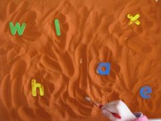 Alphabet Archaeologist - Little archaeologists (kids) sifting through the sand with a paint brush to find alphabet letters.