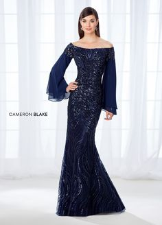 Cameron Blake 118688 is an off-the-shoulder chiffon, tulle, and intricately embroidered lace trumpet formal gown accented with heat set stones and beading that has long double layered bell sleeves, a beaded lace illusion back, and a sweep train. Mother Of Groom Dresses, Mother Of The Bride, Wedding Bridesmaid Dresses, Bridal Dresses, Wedding Gowns, Cocktail Dresses Online, Mob Dresses, Bride Gowns, Glamour