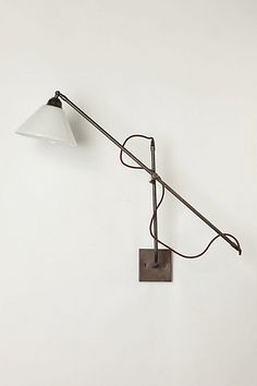 A reminder of the sleek utility of early industrial designs, this elegant handmade fixture has a timeless silhouette and features an adjustable, swinging arm and an opaque glass cone shade.