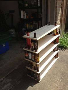 Beer Bottle Bookshelf (Big Bottles)  Made with wood planks, thread rod, washers and nuts, and a hole saw.
