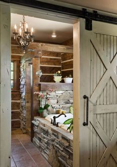 Pocatello Bath - Natural rock encloses this bathroom tub while a barn-style door provides the added privacy needed for this space. - #WesternHome