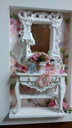 Encantador cenário Provençal Feminino, moldura em mdf branca, mini penteadeira em mdf, com gavetinhas que se  abrem e um lindo espelho provençal, colarxinho de missangas, miniaturas em resina, vasinho cerâmica, mini perfurmes e fundo em decopuage floral em tons de rosa.  Ideal para decoração de q...