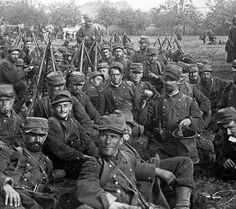 """WW1: French soldiers take a break during a march to the front, summer 1914. The Adrian helmet has yet to be introduced (it became standard issue in 1915) hence the troops wear their """"kepi"""" (cap) covered by a canvas field cover. Facial expressions reflect little enthusiasm. Most of the men in the first wave of conscripts died in the trenches within 8-10 months after this photo was taken."""