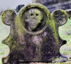 "One of the old gravestones to be found in the old churchyard.   Below the skull carving are the words ""memento more"" !"