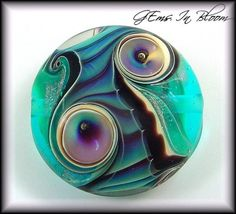 "Organic Jewel Tones Focal Lampwork Bead DESIGN: Abstract Focal Bead COLORS: Lots of designer silver glass in this piece on a transparent aqua background. Gold ribbons trail along with silver glass in a new technique. There are four encased bubble accents. APPROX SIZE: 25mm button focal bead that is 12mm thick... ""Gems In Bloom"" Lampwork Forals Flowers Jewelry-Jewellry Organics Beads"