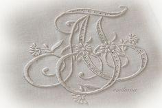 """il monogramma centrale con le iniziali degli sposi """"abbracciate"""",  ricamato a punto pieno"""