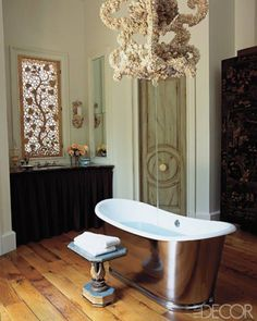 The master bath in a Sonoma County home designed by Andrew Fisher and Jeffry Weisman includes a shell-encrusted chandelier that conceals a ceiling-mounted tub filler. See more beautiful bathrooms.