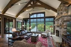 Stately living room with exposed timber trusses, stone fireplace and an amazing view of the Animas River in this 4500 sq ft. home in Durango, CO. 2017 Best Overall at Durango Parade of Homes.