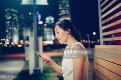 Stock Photo : Smiling office lady texting on smartphone in city