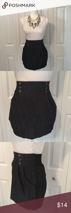 Akira Mini Skirt with Sailor Buttons and Pockets Akira mini skirt is made out of a fabric that when looked at closely looks like a dark denim. Skirt has two angled pleats in front of the two side pockets giving the skirt amazing shape around the hips. Three buttons on either side have anchors on them giving a nautical feel if wanted. Back waist of skirt has a wide elastic band that comes together at the exposed zipper. Small area (about an inch) where it appears double stitching occurred…