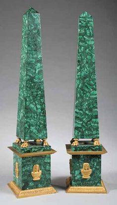 A Large Pair of Bronze-Mounted Malachite Obelisks, on paw feet, the plinths decorated with masks of Cleopatra, resting on square conforming plinths, height 31 in., 7 in. square at base.