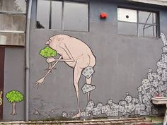 """Cagacemento by NemO's in Milan, Italy, 2010. Street art of a human eating trees and excreting houses. Artist: """"Because I come from a small city surrounded by countryside this big city seemed like a desert of cement to me, the skyline was barely visible! Every huge metropolis seems like a stain of oil that looks still but is slowly expanding and gulping everything down! I felt the necessity to show and tell the story of the expanding city that feeds on nature and expels cement waste!"""""""