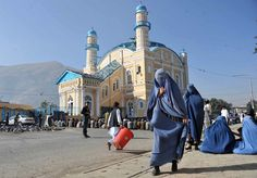 Afghan women walk past Muslim devotees praying to celebrate Eid al-Adha at the Shah-e Do Shamshira mosque in Kabul