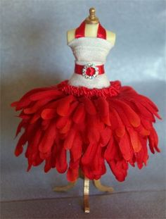 Rose Red. NEW STOCK. Striking STUNNING dress in pure white and Christmas red. Crystal buckle that twinkles on the red ribbon belt. Tumbling red silk petal skirt. Lovingly created on a 5 inch top quality resin mannequin.