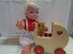 Eine alte Schildkröt Puppe mit kleinem Clemens Teddy und einem Puppenwagen
