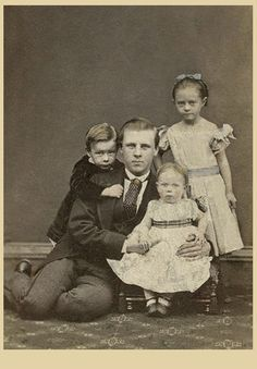 Beautiful portrait of a father and his three children.  The informal pose is unusual for that time period.  And yet it shows the love of this father who doesn't mind getting down on the floor with his little ones.  I love the way the boy is hugging his father from behind and the way the father is leaning into his girls, it displays such tenderness. Glasgow, Scotland.  ca.
