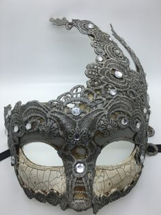 Grey antiqued Mardi Gras mask with rhinestones and ribbon ties. Each one is a little different and colors and tints may vary a bit.