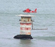 Mile Rock Lighthouse at the entrance of the Golden Gate in San Francisco, CA. top portion removed in 1966. With helicopter
