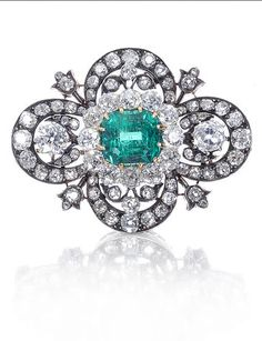A late 19th century emerald and diamond brooch, The central rectangular cut-cornered step-cut emerald, within a quatrefoil frame set throughout with cushion-shaped, old brilliant and rose-cut diamonds, with foliate diamond accents, mounted in silver and gold, diamonds approximately 6.80 carats total, brooch length 4.2cm, cased by Cartier