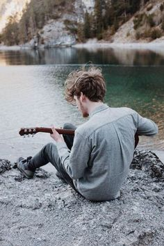 Guy playing guitar in front of water. Thats something I would do, I would love it.